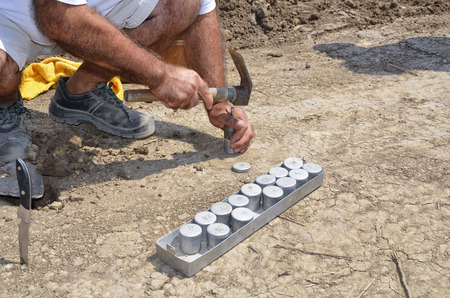 Collecting underground samples from drilled special prepared assessment point. The underground samples will be used for lab analysis. Stock Photo
