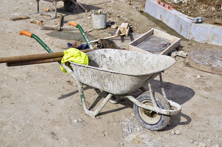 work area: wheelbarrow to work area at a building site with tools Stock Photo