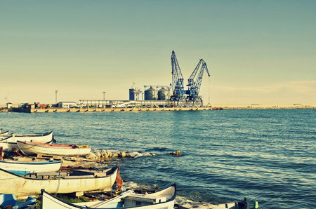 commercial docks: Commercial docks at sunset with a boat and cranes ,selective focus, Balchik, Bulgaria