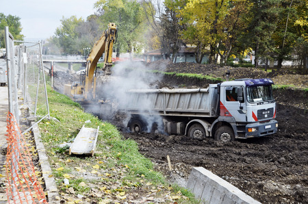 The dirty truck which got stuck in the mud ,smoke from tire rotation,construction along the river,excavator Reklamní fotografie