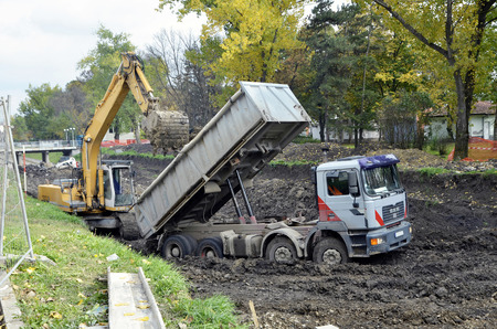 The dirty truck which got stuck in the mud ,construction along the river,excavator