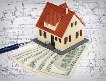 model house: dollar banknotes and a model house on a construction plan for house building; concept of buying a house