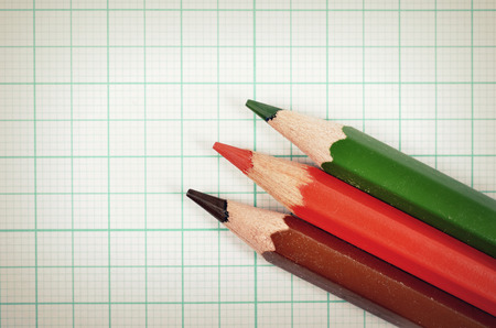 Colored pencils with graph plotting paper for background