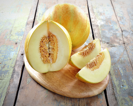 Fresh melons sliced on the  wooden table.