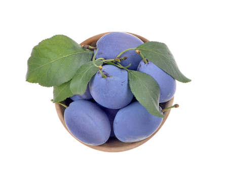 Delicious blue plums in a wooden bowl, isolated white background Stock Photo