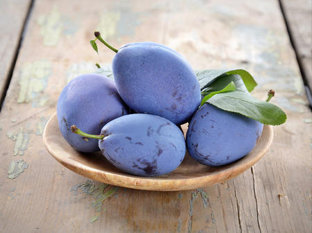 Delicious blue plums in a wooden bowl, selective focus