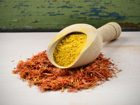 saffron powder and petals in a wooden spoon on wood background Stock Photo