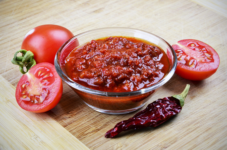 Tomato chutney in a glass bowl on a wooden background