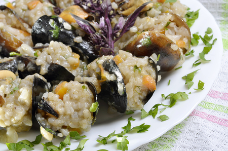 Risotto with mussels  in the plate on a  tablepaella,selective focus