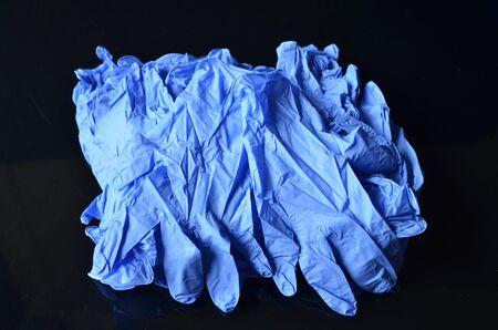 Coronavirus concept.Disposable blue medical latex gloves on black background. Hygiene rules during the coronavirus epidemic.Healthcare equipment concept.
