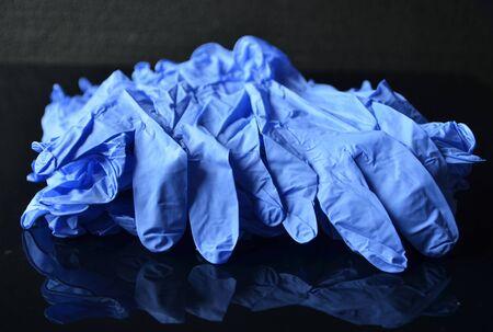 Coronavirus concept.Disposable blue medical latex gloves on black background. Hygiene rules during the coronavirus epidemic.Healthcare equipment concept. Stock fotó