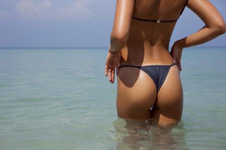 Mooie slanke rug van de close-up mooie luxe van een mooie vrouw in zwempak het stellen in het zeewater. Sexy gebruinde lichaam, platte buik, perfect figuur. Rust op een tropisch eiland. Sexy billen. Met copyspace Stockfoto