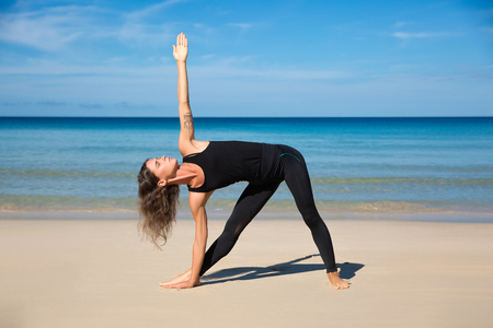 Healthy yoga exercise on the beach, slim sporty body training, leisure and meditation, vacation, sport, health care concept, over natural background blue sky and sea. Ashtanga vinyasa