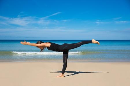 yogini: Beautiful sporty fit yogini woman practices yoga asana Virabhadrasana - warrior pose , on the beach Stock Photo