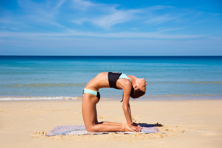 Beautiful sporty fit yogini woman practices yoga asana Virabhadrasana - warrior pose , on the beach Stock Photo