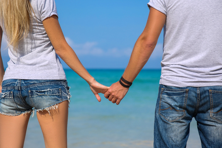 fulfill: Happy couple walking hand in hand on white sand beach