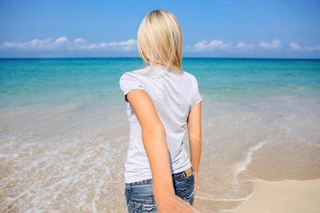 Woman holding man hand smile on beach ocean leads summer vacation follow tourist Stock Photo