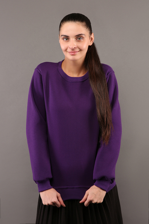 sweatshirts: Young hipster girl wearing blank purple cotton sweatshirt with copy space for your design or logo, mock-up of purple template womens hoodie, grey wall in the background
