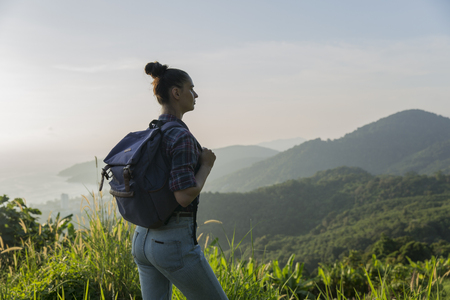 basque country: Hipster young girl with backpack enjoying sunset on peak of foggy mountain. Tourist traveler on background view mockup.