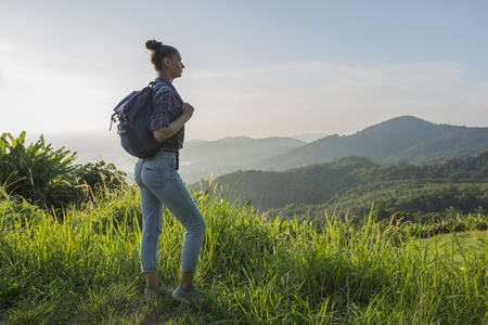 photo edges: Hipster young girl with backpack enjoying sunset on peak of foggy mountain. Tourist traveler on background view mockup.