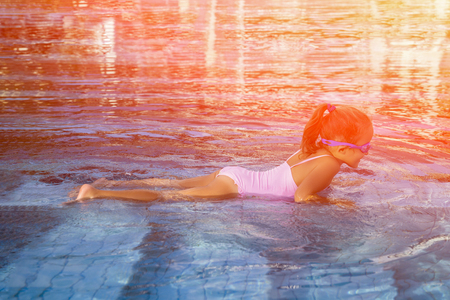 bath: Cute girl with goggles in swimming pool. Toned