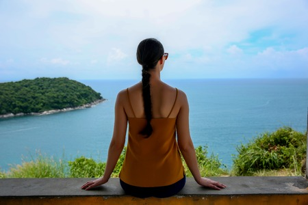 Young woman sitting and relaxing on a natural coastal rock, contemplating the sea against a sky. Well being healthy lifestyle