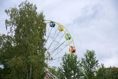 Ferris wheel on cloudy sky and green Trees background Фото со стока