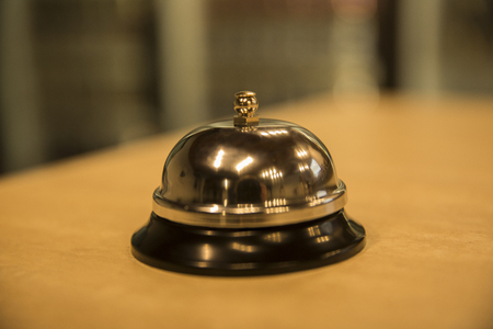 Vintage hotel reception service desk bell. Old retro style filtered photo Фото со стока