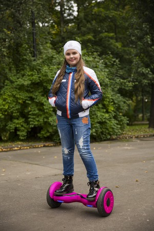 Child on hover board. Kids riding scooter in park. Balance board for children. Electric self balancing scooter on city street. Girl learning to ride hoverboard. Modern gadgets for school kid.