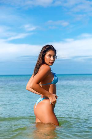 Schönes Mädchen, das auf dem Strand in der heißen Sonne, Außenporträt aufwirft Standard-Bild