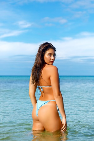 Belle fille posant sur la plage sous le soleil chaud, portrait en plein air