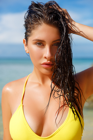 Close up portrait of attractive young woman on the beach. Young caucasian female model posing on the sea shore. Фото со стока