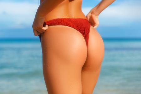 Culo e fianchi ideali per la donna: perfetto programma anticellulite e cura della pelle. Foto della spiaggia dell'oceano. Archivio Fotografico