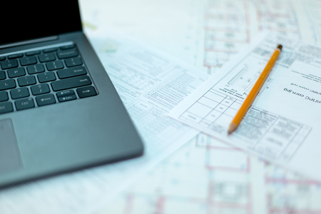 Pencil and computer laptop on architectural drawing paper for construction