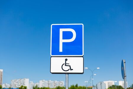 Disabled parking space and wheelchair way sign and symbols on a pole warning motorists
