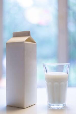 Carton box and glass of milk on table in kitchen Фото со стока - 131812710