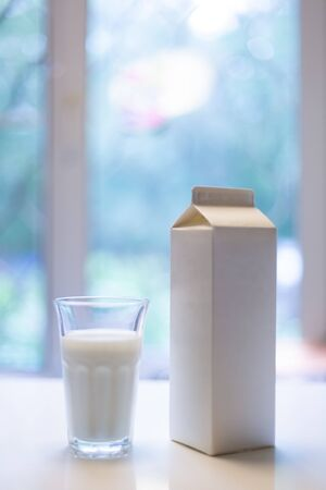 Carton box and glass of milk on table in kitchen Фото со стока - 131813016