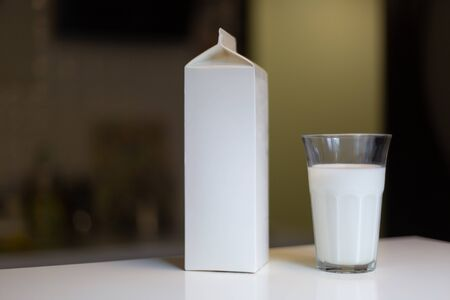 Carton box and glass of milk on table in kitchen