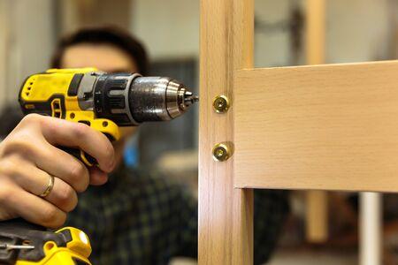 Bouwmeester met boormachine. Professionele timmerman die met hout werkt en gereedschappen in huis bouwt.