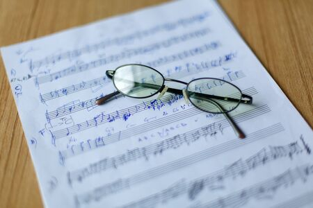 Ancient musical manuscript, glasses in the background Imagens