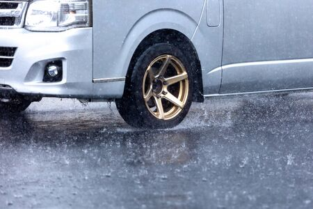 motion car rain big puddle of water spray from the wheels Foto de archivo
