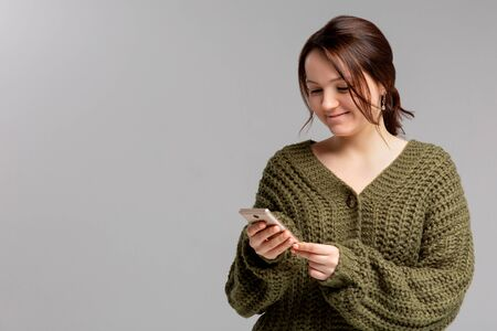 Joyful emotive young european woman with stylish earrings, holding smartphone and smiling cheerfully at camera while retelling interesting article to friend