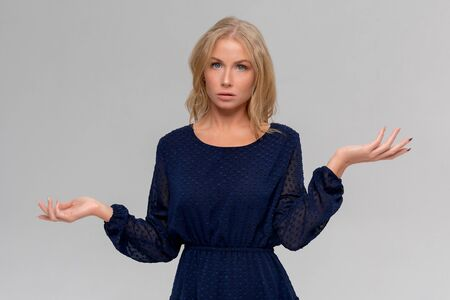 Studio portrait of cute puzzled hesitant young woman shrugs shoulders, does not know what happened. Pretty attractive woman doubting isolated on gray background