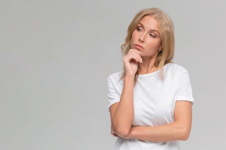 Close up portrait of bored young woman in white t-shirt throw their hands up, staring with indifferent, watching tv at home during quarantine, dont know what do, feel sad, isolated on gray background Stock fotó