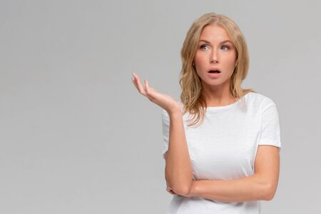What wrong. Ambushed shocked confused young girl coworker shrugging hands spread sideways full disbelief asking question questioned perplexed understood situation, white background