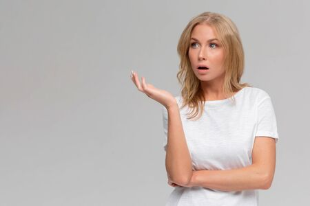 Wtf are you talking about. Portrait of displeased pissed european female, standing in angry pose, shaking hands and gesturing, being clueless and questioned, standing puzzled over grey wall