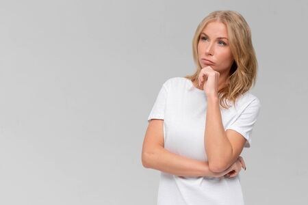 Hmm, girl needs to think carefully. Portrait of doubtful thoughtful caucasian female coworker, holding hand on chin, frowning while focusing on task, solving issue over gray wall