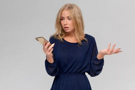 Portrait of confused and questioned good-looking female student in casual outfit, showing clueless and unaware gesture, gazing with no clue at smartphone screen, cannot understand message 版權商用圖片