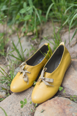 womans: Yellow womans shoes on a grass and stones Stock Photo