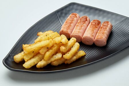 food french fries with sausages on a black plate on a white background
